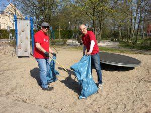 Hans Werner Pollack und Thomas Semmelmann sammeln Müll auf dem Spielplatz